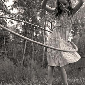Young Girl Twirling Hula Hoop Outdoors In Sepia For Vintage Look by CherylCasey