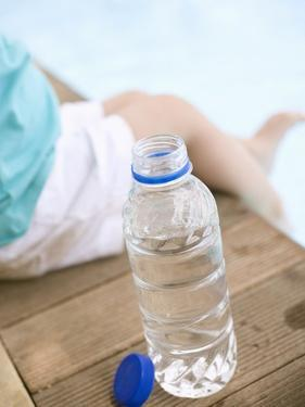 Child Sitting Beside Bottle of Water on Edge of Pool