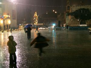Children Play in the Rain in Front of the Church of the Nativity in Bethlehem on Christmas Eve