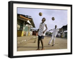 Children Play Soccer on a Street
