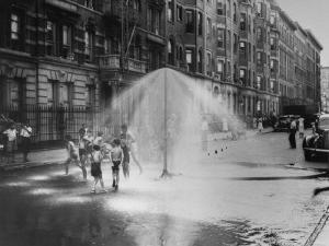 Children Running Around under Sprinkler in Street to Cool Off During Summer, in South Harlem