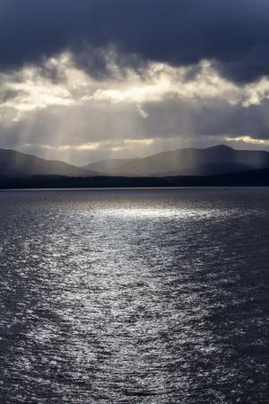 https://imgc.allpostersimages.com/img/posters/chile-patagonia-strait-of-magellan-tierra-del-fuego-rays-of-sunshine-over-the-fjords-and-sea_u-L-Q1H21JU0.jpg?artPerspective=n