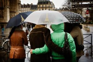 A Couple Embrace under an Umbrella Outside the Notre Dame in Paris, France by Chris Bickford
