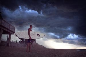 A Man Carries His Surfboard Along the Beach on the Outer Banks of North Carolina by Chris Bickford