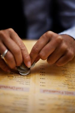 A Man Holds Coins in His Hand While Looking at a Restaurant Menu in Paris, France by Chris Bickford