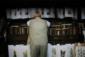 A Man Rests on Drawings, Prints, and Books in Paris by Chris Bickford