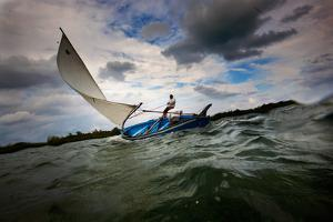 A Man Sails a Boat Off the Cayman Islands in the Caribbean by Chris Bickford