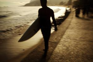 A Surfer Walks Along Ipanema Beach in Rio De Janeiro in the Afternoon by Chris Bickford