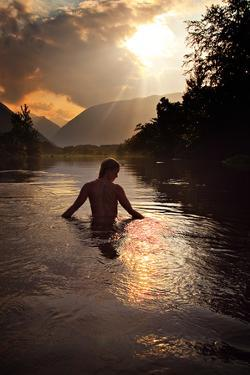 A Woman Bathes in the Waipi'O River at Sunset by Chris Bickford
