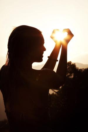 A Woman Captures the Sun in Her Hands by Chris Bickford
