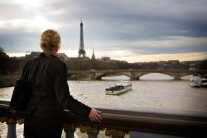 A Womn Looks at the Seiene River and the Eiffel Tower in Paris, France by Chris Bickford