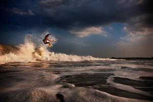 A Young Man Surfs on a Wave on the Outer Banks of North Carolina by Chris Bickford