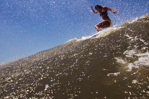 A Young Woman Surfs on a Wave on the Outer Banks of North Carolina by Chris Bickford