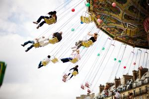 Adults and Children Enjoy a Swing Ride in Paris, France by Chris Bickford