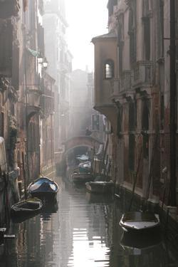 Boats Floating in a Narrow Canal Between Buildings in Venice, Italy by Chris Bickford
