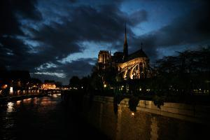 Notre Dame Sits Next to the Seine River at Night in Paris, France by Chris Bickford