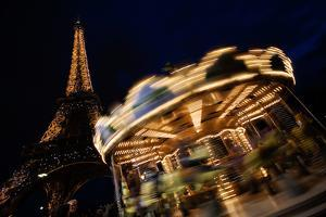 The Famous Eiffel Tower and a Carousel Illuminated at Night in Paris, France by Chris Bickford