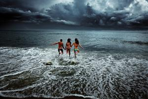 Two Young Women and a Young Man Run into the Ocean on the Outer Banks of North Carolina by Chris Bickford