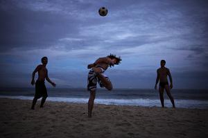 Young Men Play Soccer on Copacabana Beach in Rio De Janeiro by Chris Bickford