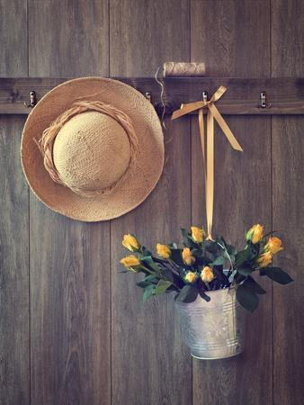 Rustic Shed Door with Hanging Straw Hat and Bucket of Yellow Roses