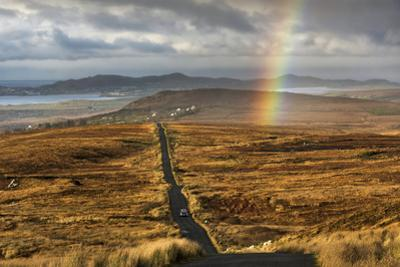 Rainbow over Long Straight Country Road in a Winter Landscape by Chris Hill