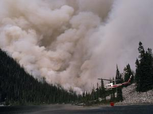 Helicopter Carrying Water from a River to Fight a Forest Fire by Chris Johns