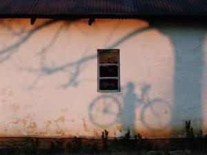 Shadow on a Wall of a Man Holding a Bicycle by Chris Johns