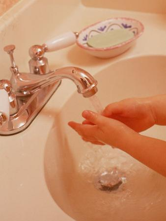 Young Girl Washing Hands in Sink