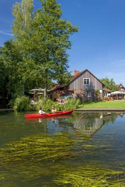 Europe, Germany, Brandenburg, Spreewald, Leipe, Traditional Houses at Water Channel, Canoeists by Chris Seba