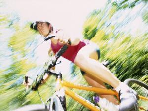 Action of Female Cyclist on Mountain Bike Riding Throught the Woods, Rutland, Vermont, USA by Chris Trotman