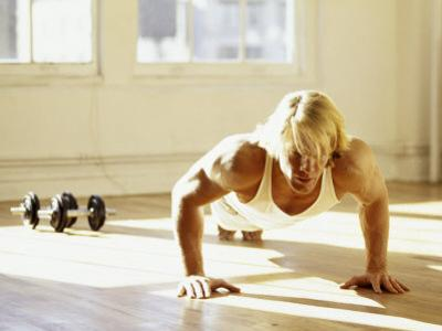 Young Man Preforming Push Up Exercise in Gym, New York, New York, USA by Chris Trotman