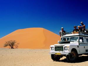 Men on Four Wheel Drive Vehicle at Dune 45 in Namib Nauklaft National Park, Sossusvlei, Namibia by Christer Fredriksson