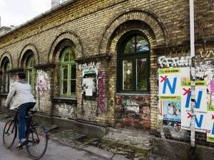 Cyclist in Freetown Christiania, with Anti European Union Posters on Wall by Christian Aslund