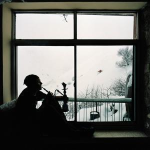 Man Smoking Water Pipe by Window, Alborz Mountain Range by Christian Aslund