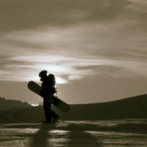 Silhouetted Snowboarder Hiking by Christian Aslund