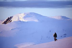 Snowboarder Walking on Slopes during Midnight Sun. by Christian Aslund