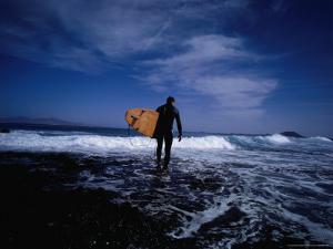 Surfer Entering Surf, Isla De Fuerteventura, Canary Islands, Spain by Christian Aslund
