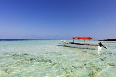 Small boat in crystal clear water, Pingwe, Island of Zanzibar, Tanzania, East Africa by Christian Kober