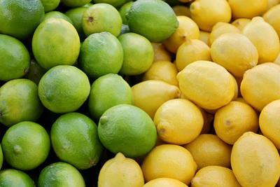 Pile of Fresh Yellow Lemons and Green Limes at Farmer's Market by Christin Lola