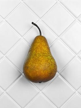 Pear in front of white background by Christopher Stevenson