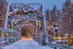 Christmas decorations adorn the historic one lane Swan River Bridge in Bigfork, Montana, USA by Chuck Haney