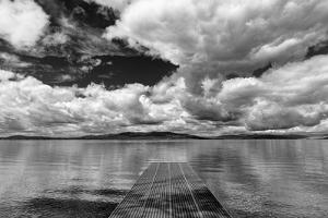 Dock reaches out into Skidoo Bay in Flathead Lake near Polson, Montana, USA by Chuck Haney