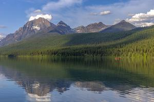 Fishing from a red canoe on the calm waters of Bowman Lake in Glacier National Park, Montana, USA by Chuck Haney