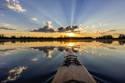 Kayaking into sunset rays on McWennger Slough, Kalispell, Montana, USA by Chuck Haney