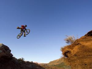 Mountain Biker Catches Air at Rampage Site near Virgin, Utah, USA by Chuck Haney