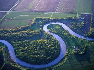 Red River Runs in Farm Country on North Dakota and Minnesota Border, USA by Chuck Haney