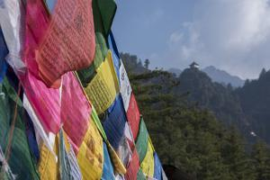 Bhutan, Paro. Colorful prayer flags in front of small outbuilding of the Tiger's Nest. by Cindy Miller Hopkins