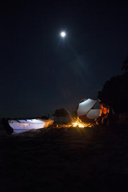 An Expedition Photographer Tends a Campfire on the Remote Beaches of Isla Bastimientos by Clare Fieseler
