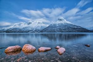 Blue sky at dusk and snowy peaks are reflected in the frozen sea at Oteren Storfjorden Lapland Lyng by ClickAlps