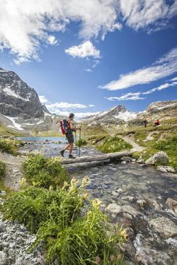 Hiker crossing a stream Engadine Canton of Grisons Switzerland Europe by ClickAlps